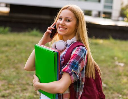 Female student with headphones using mobile phone  outdoor.