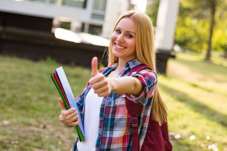 Portrait of beautiful female student showing thumb up while standing outdoor.