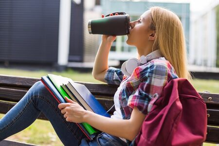 Female student with headphones  drinking coffee outdoor.