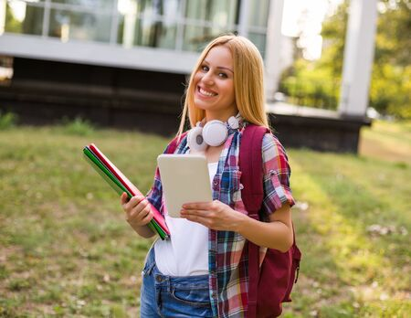 Female student with headphones using digital tablet outdoor.