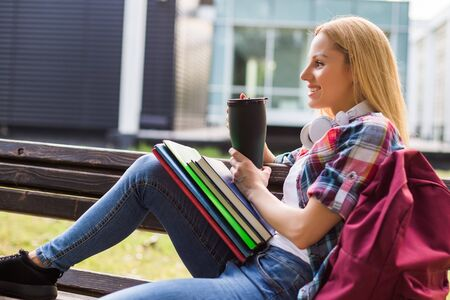 Female student drinking coffee outdoor.