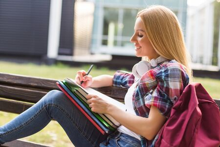 Female student studying while spending time outdoor.