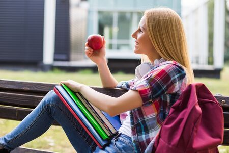 Female student eating apple while spending time outdoor.