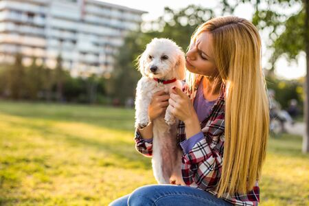 Woman scolding her Maltese dog while they spending time in the park.