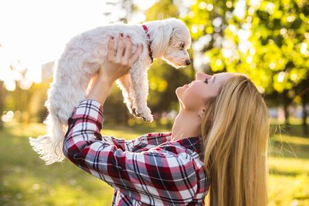 Beautiful woman spending time with her Maltese dog outdoor.