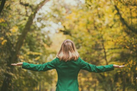 Woman with her arms outstretched enjoys in autumn while standing in the park.