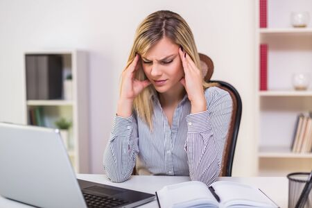 Businesswoman having headache while working in her office.