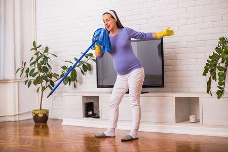 Mooie zwangere vrouw geniet van het schoonmaken van haar huis.
