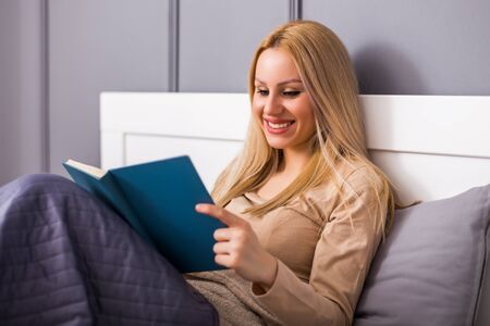 Beautiful woman enjoys reading a book at her bedroom .