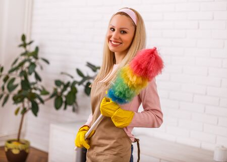 Beautiful housewife enjoys cleaning with duster her home.