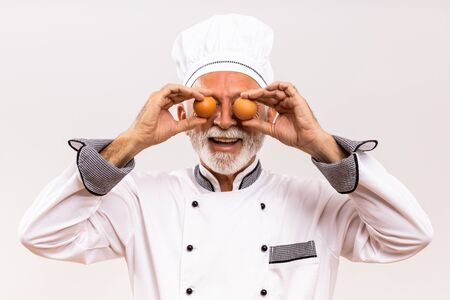 Image of happy senior chef covering eyes with eggs on gray background. Banco de Imagens