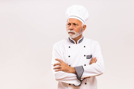 Portrait of angry senior chef on gray background.