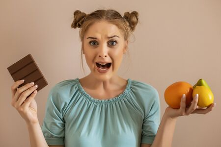 Cute woman is shouting because she is  tired of dieting and  eating fruit.Toned image.