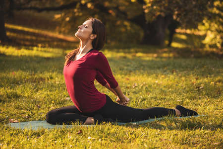Beautiful woman doing yoga in the nature,variation of Salabhasana/Locust Pose