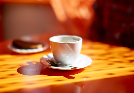 Coffee cup on the table at the evening sunlight