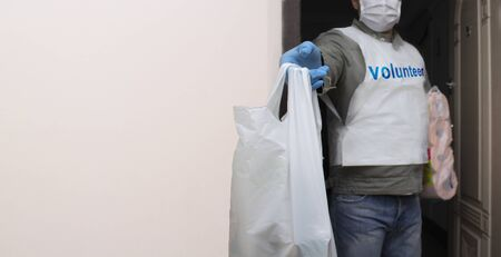 Volunteer carrying necessities for citizens in home self isolation.Young Man with bag of groceries for Senior people during Corona virus Pandemic.Town in quarantine due to Covid-19 flue infection Stok Fotoğraf