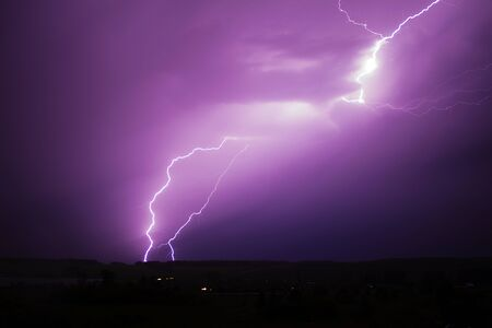 Huge lightning strikes the forest and field. Night storm with thunder and lightning.