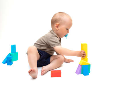 baby playing with toys on a white background. A funny little child plays with colorful cubes, builds a house from the details of the constructor. Concept of early childhood development