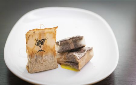 On a white plate are used tea bags, a used tea bag with a drawn sad face. Stock fotó