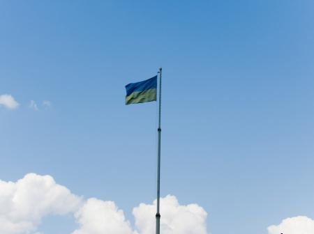 cossacks: Yellow-blue Ukrainian flag flies on the sky background Stock Photo