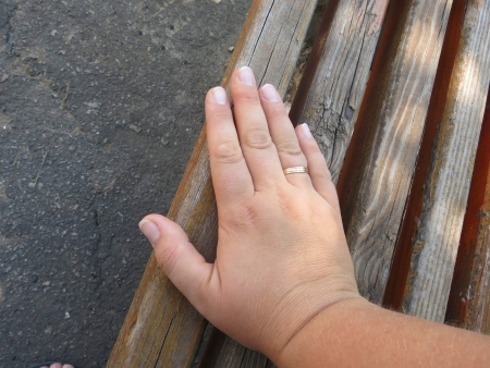 ring finger: Womans hand with a wedding ring on the ring finger rests on a wooden bench