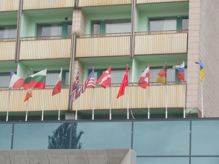 flags of the different countries stand in a row at the entrance to the building photo