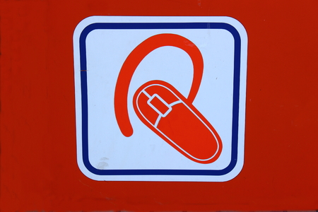 mobile headsets: Sobre un fondo naranja cuadrado blanco donde los auriculares para m�vil y fotos Foto de archivo
