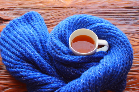 cup of coffee in a scarf on a wooden board photo