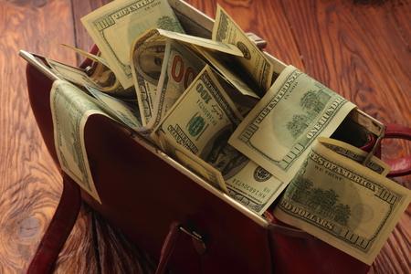 remuneraciones: de pie sobre una tabla de madera bolsa con d�lares Foto de archivo