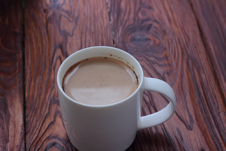 cappaccino: on a wooden board with white cup of coffee with milk Stock Photo