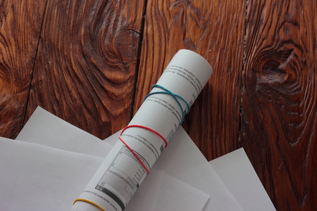 nformation: lying financial papers rolled into a tube with rubber bands Stock Photo