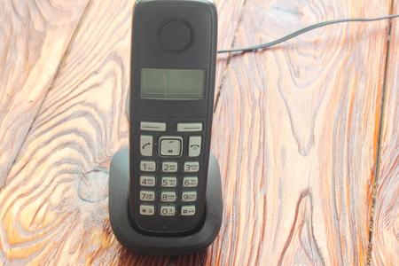 caller: on a wooden board is a cordless phone on the charging cradle