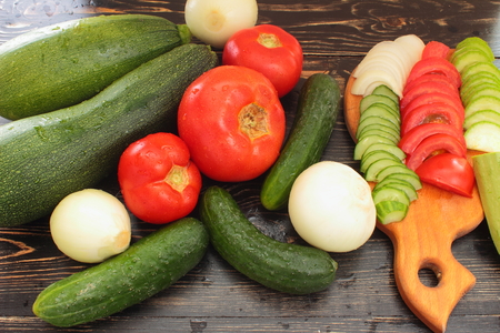 healthy product: whole and sliced cucumbers tomatoes zucchini onions