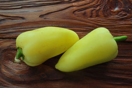 ailment: is two sweet pepper on a wooden board