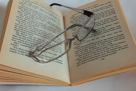 vision repair: glasses lying on an open book Stock Photo
