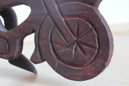 invents: close-up of a wooden wheel bicycle brown