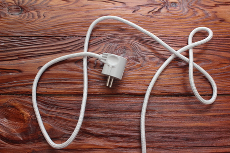power cord: on a wooden board is the power cord white