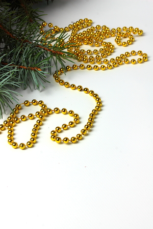 christmas beads: spruce branch decorated with Christmas beads on a white background Stock Photo