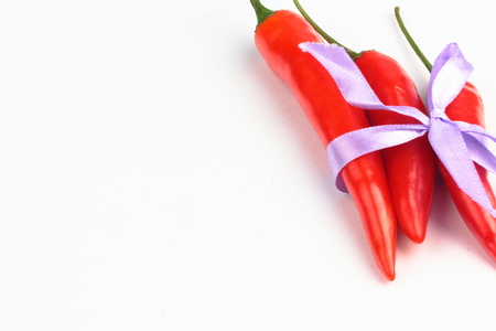 spicey: three red peppers decorated with ribbon isolated on white background Stock Photo