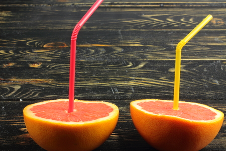 vitamin c: two halves of grapefruit on a wooden board with tubes inserted in them Stock Photo