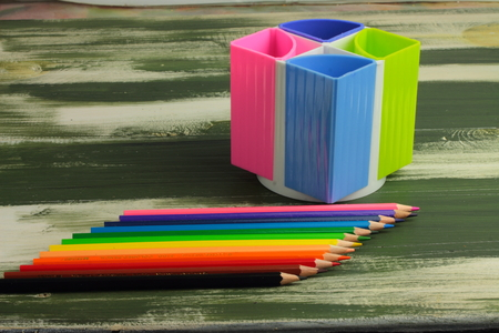 fournitures scolaires: sur une planche en bois et des crayons de couleur debout pour les fournitures de bureau