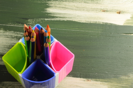 colored school: on a wooden board and colored pencils stand for office supplies