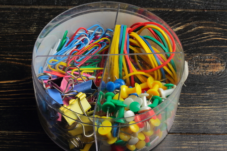 on a wooden board in a plastic box are rubber bands, paper clips, binders, buttons cloves