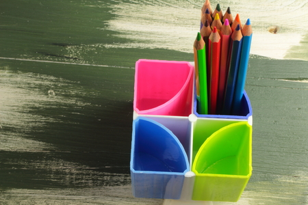 supplies: on a wooden board and colored pencils stand for office supplies
