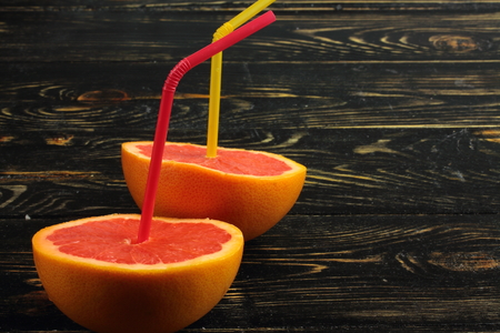 c: on a wooden board cut in half grapefruit with cocktail straws Stock Photo