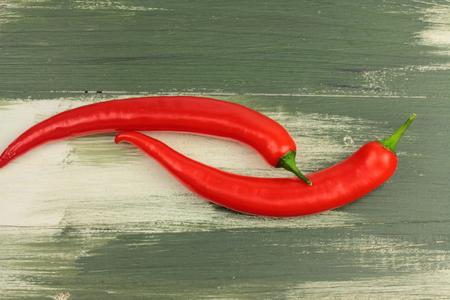 spicey: lie on a wooden board Two red peppers