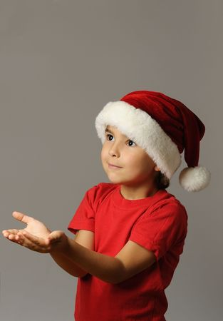 red tshirt: Kid in Santa hat and red tshirt  holding an imaginary gift