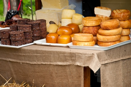 romanian: Traditional Romanian cheese varieties displayed by a farmer at a medieval fair Stock Photo