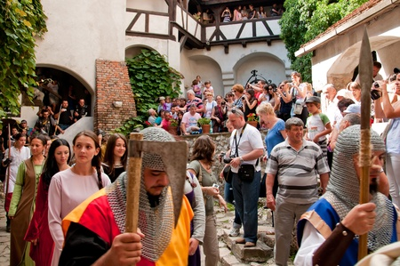 Actors dressed in medieval costumes acting in front of an audience at Bran castle in Romania