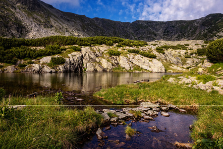 Serene cauldron in the high mountains of central Romania with glacial lake and rock formations